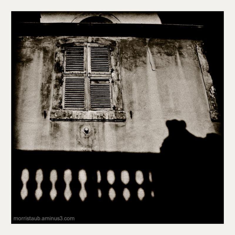Old shutters and deep shadows from a balcony.
