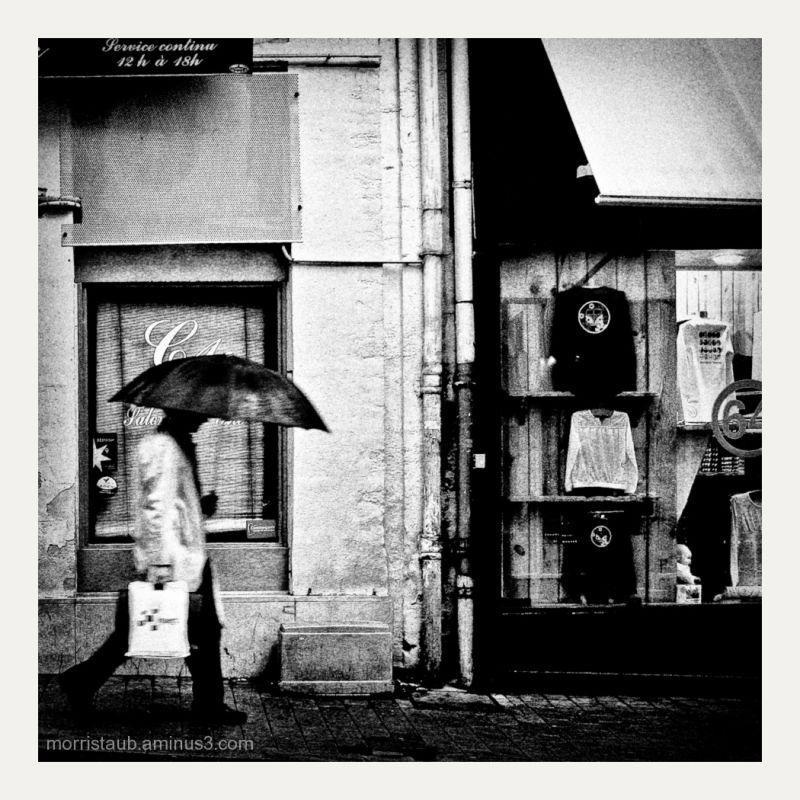 Man holding umbrella walking in street.