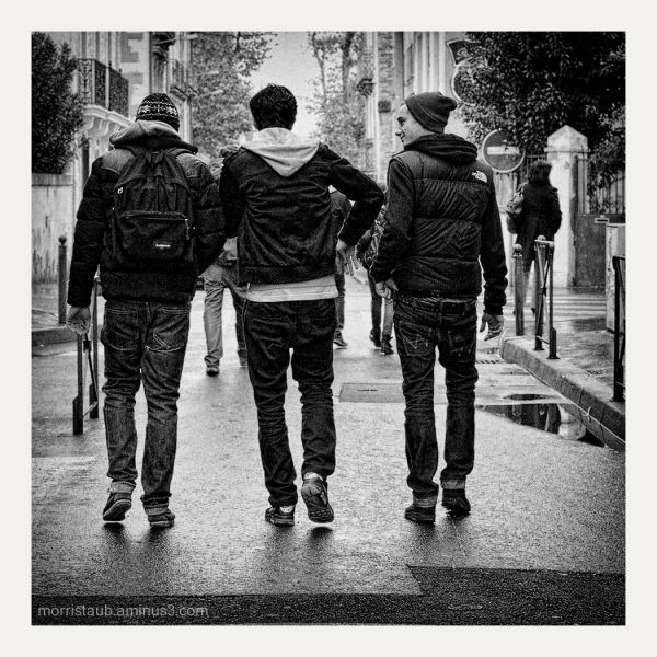 Three friends walking and talking together.