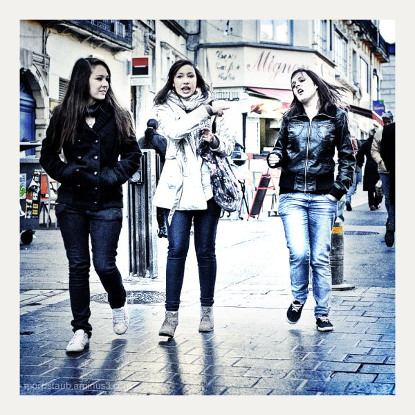 Three young women walking in the street.