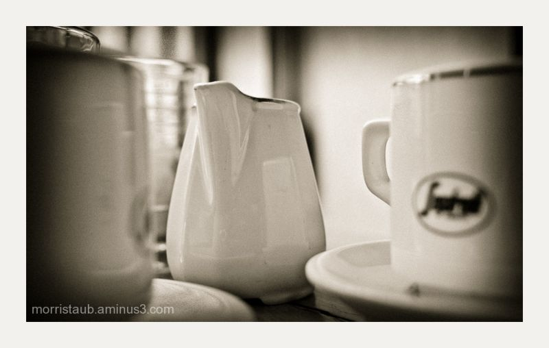 Table at cafe with milk pot and coffee mugs.
