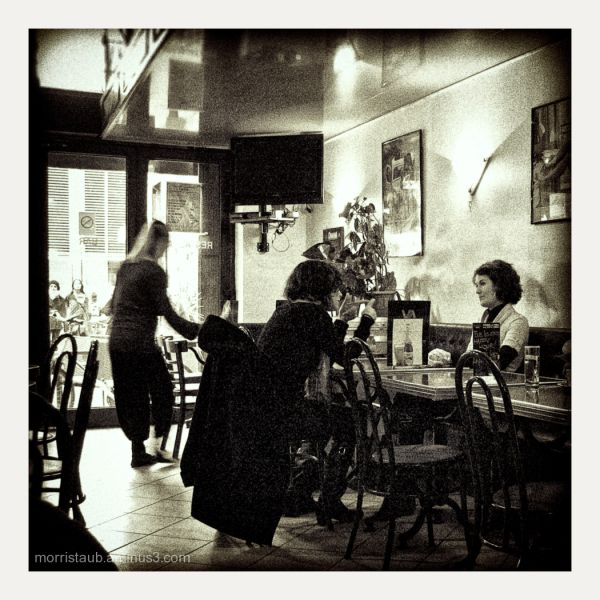 Two girls talking, waitress cleaning, in a cafe.