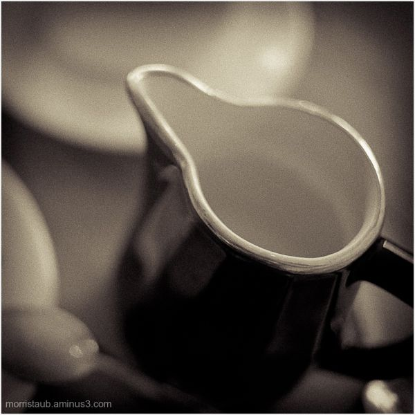 Milk pot near coffee mugs on table in cafe.