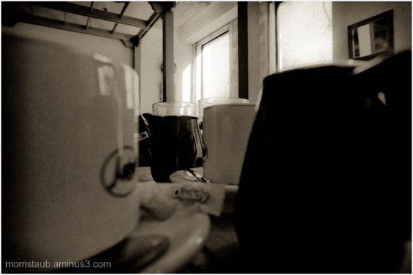Cafe scene of mugs milk and light thru windows.