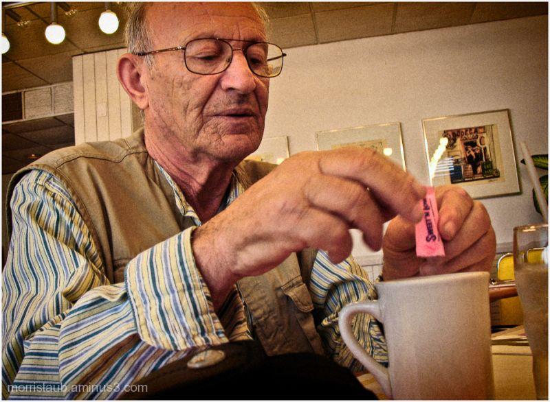 Man adding sweet 'n' low to coffee.