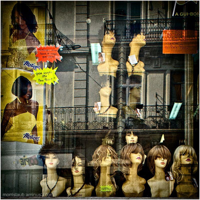 Wigs for women on plastic heads in store window.