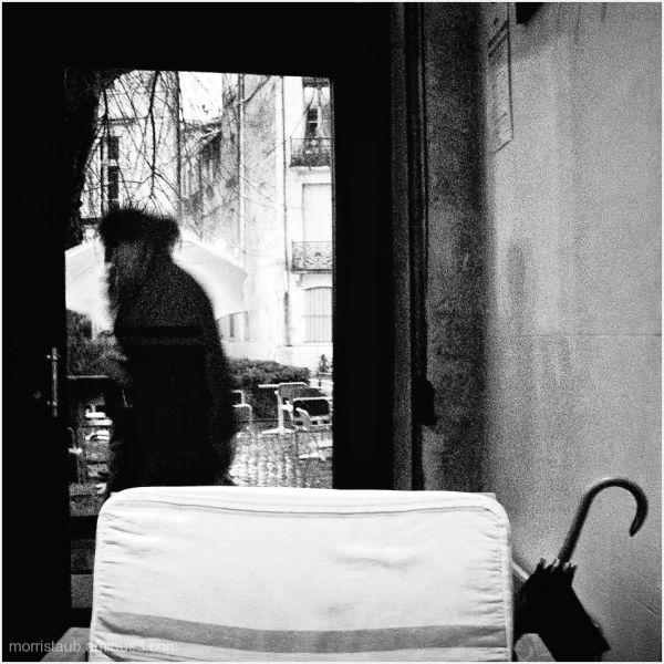 Woman standing in cafe doorway.
