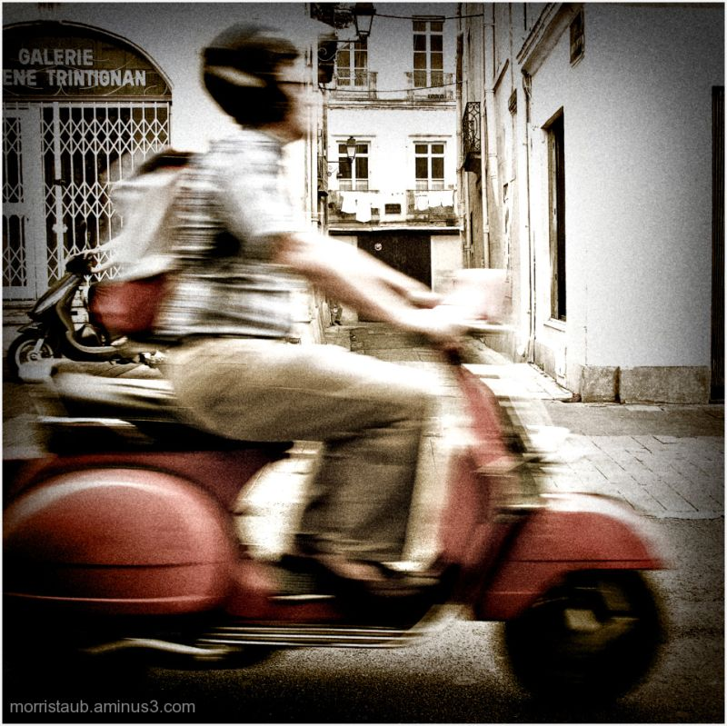 Man riding by on a scooter.