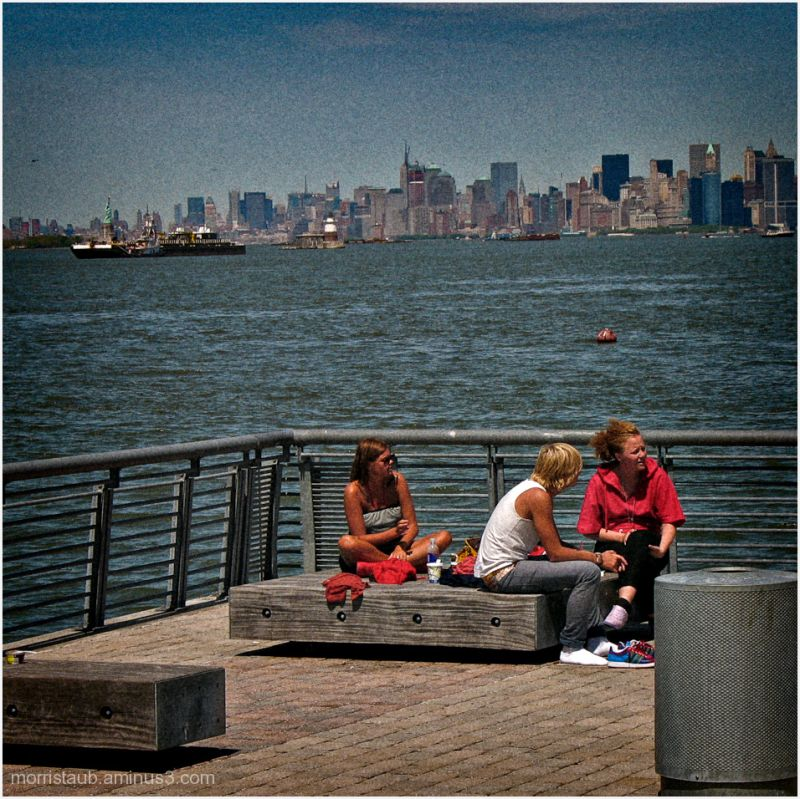 Three people sitting in the sun in NY harbor.