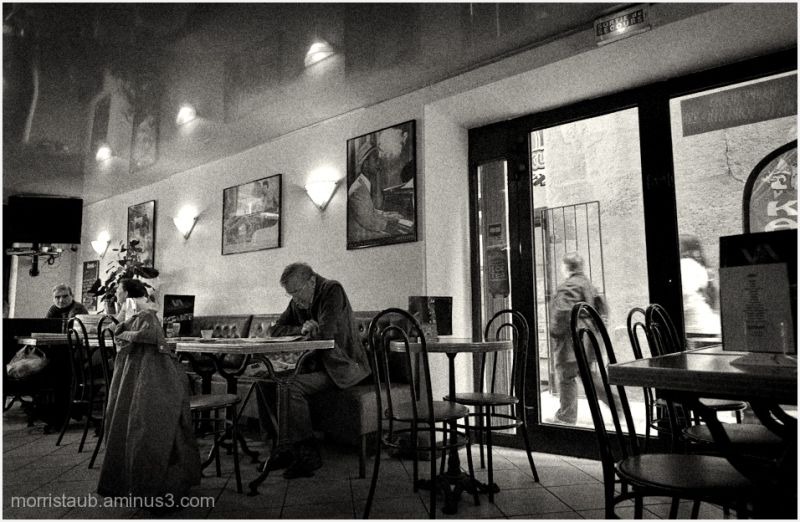 Man reading newspaper in a cafe in France.