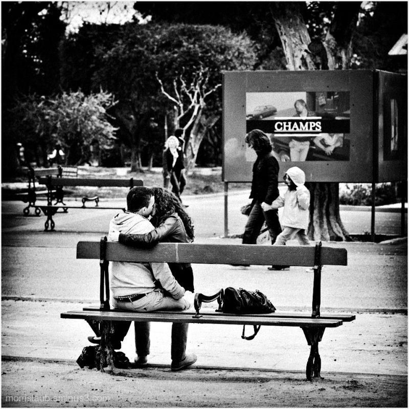 Young couple kissing on a public bench.