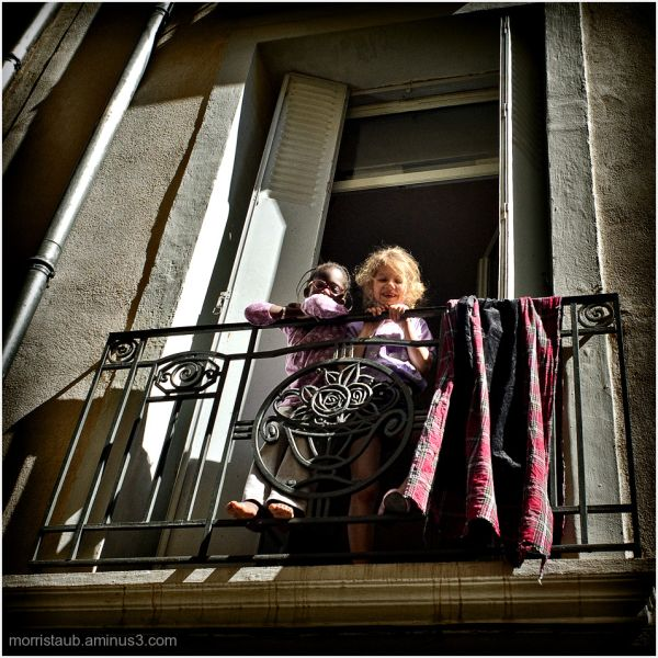 Two young smiling girls on a balcony.
