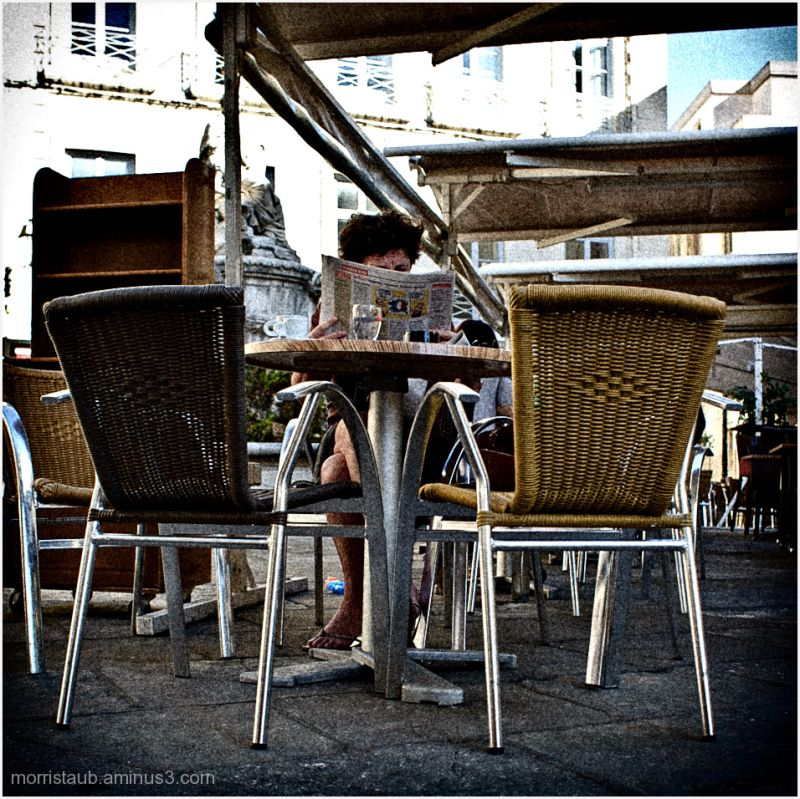 Woman reading newspaper with morning coffee.