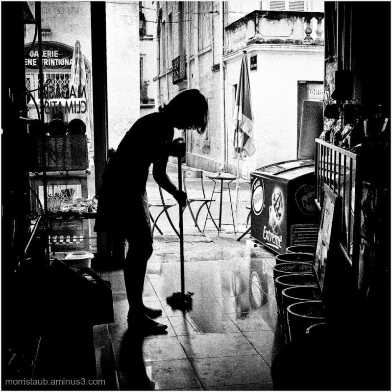 Store owner washing the floor of her store.