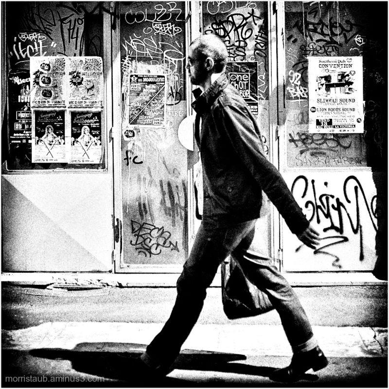 Man walking past wall of graffiti.