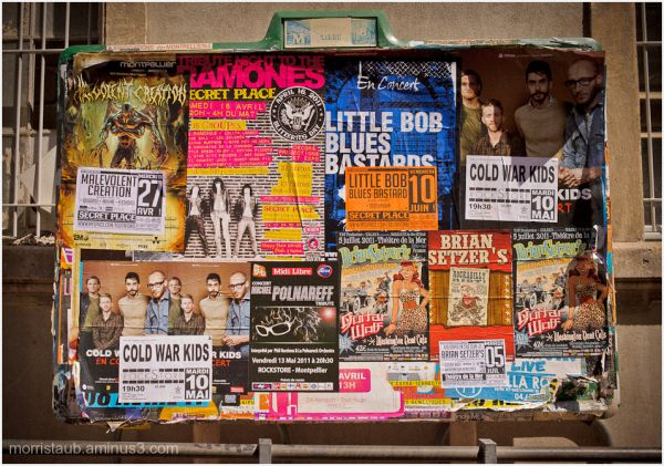 Group of posters on a street billboard.