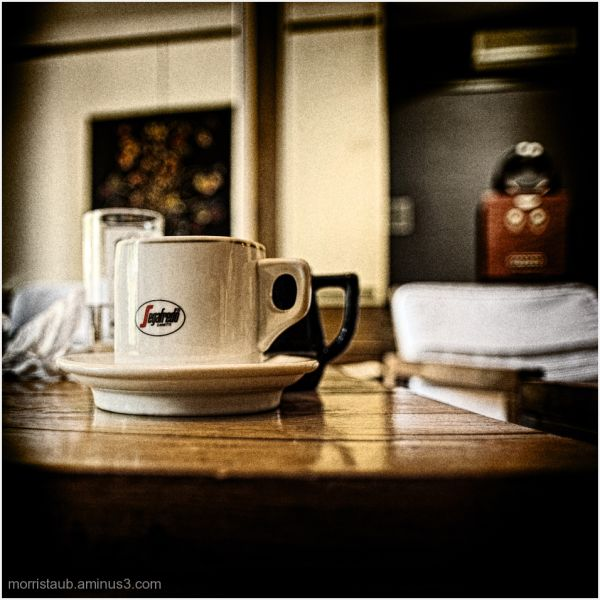 Coffee mug, milk pitcher, water glass in cafe.