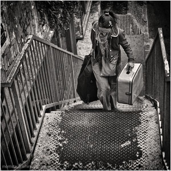 Woman with travel bags walking up stairs.