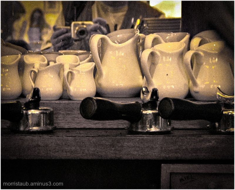 Bunch of milk pitchers in a cafe.