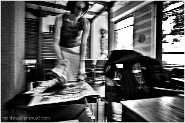 Woman in cafe looking for a newspaper.