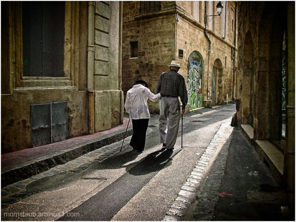Old couple strolling on old french village street.