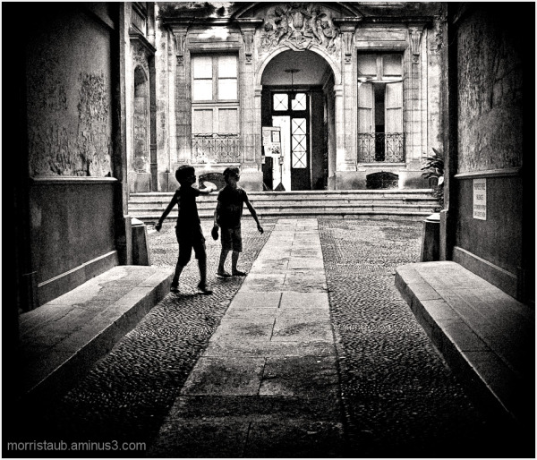 Two boys playing paddle ball in an old courtyard.