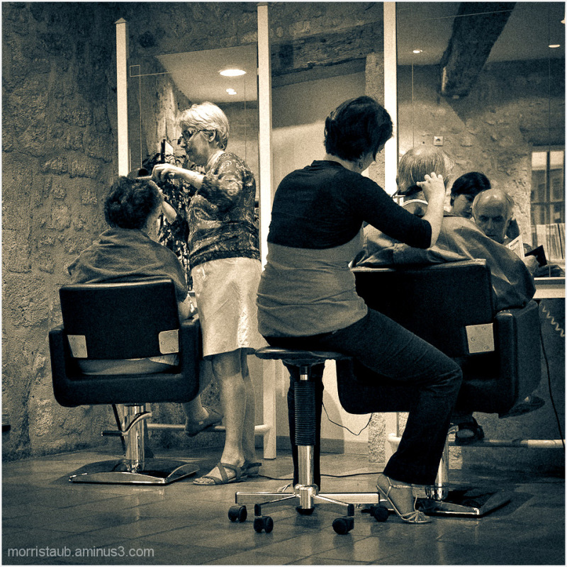 Two women cutting hair in a salon.