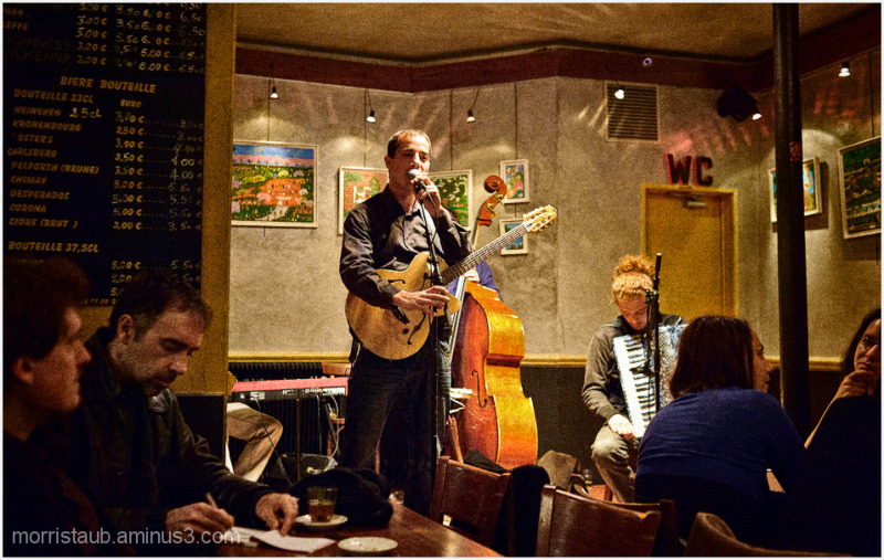 Musician in Paris bistrot about to perform.