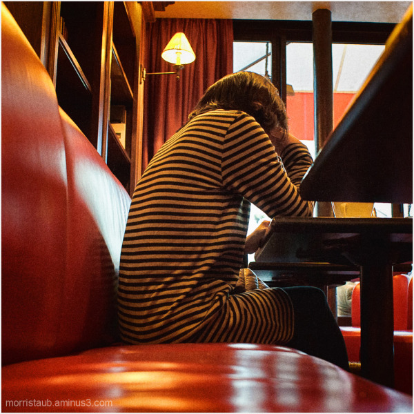 Woman in striped dress reading in a cafe.