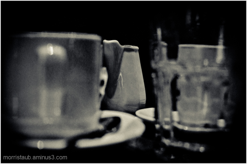 Coffee mugs and milk pitcher on table in a cafe.