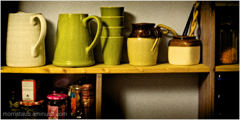 Pitchers, mugs, and spices on kitchen shelves.