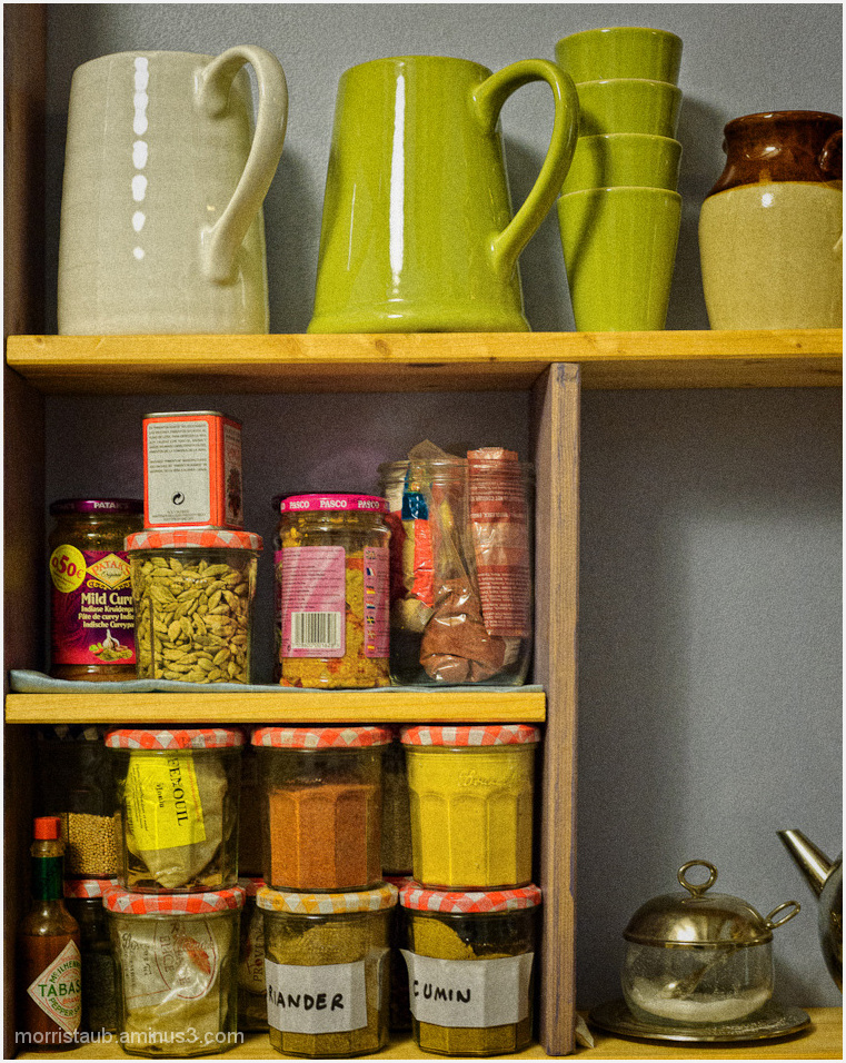 Kitchen shelf with spices, mugs, pitchers.