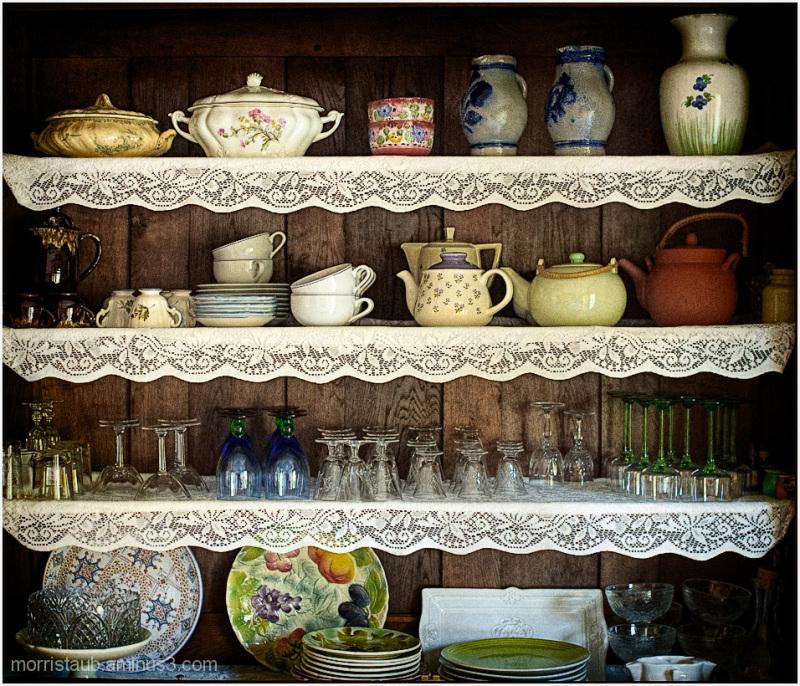 Hutch full of mugs, dishes, mugs, and glasses.