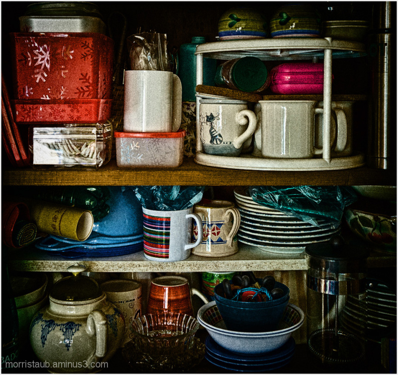 Kitchen cupboard with glass plates, mugs, bowls.