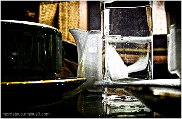 Cafe table with coffee, glass and milk pitcher.