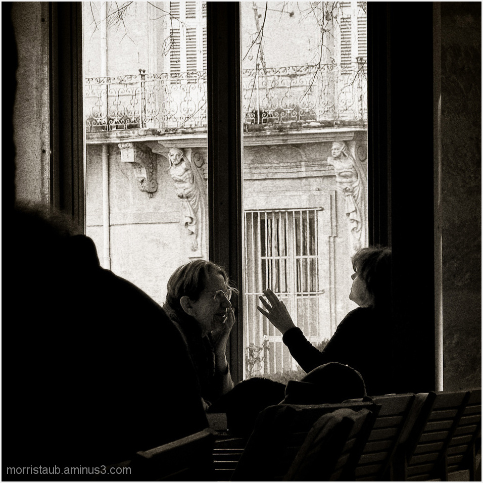 Two women talking in a french cafe.