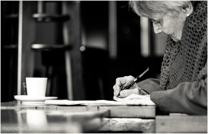 Woman in shawl writing in a cafe.