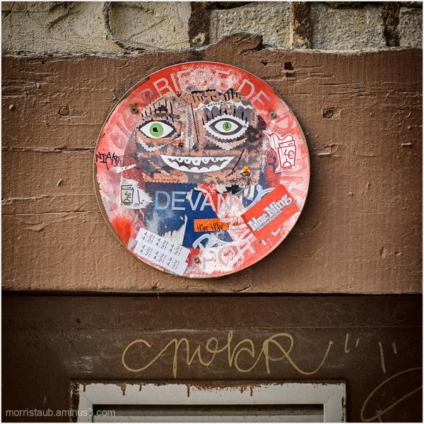 Round sign above door in the street.