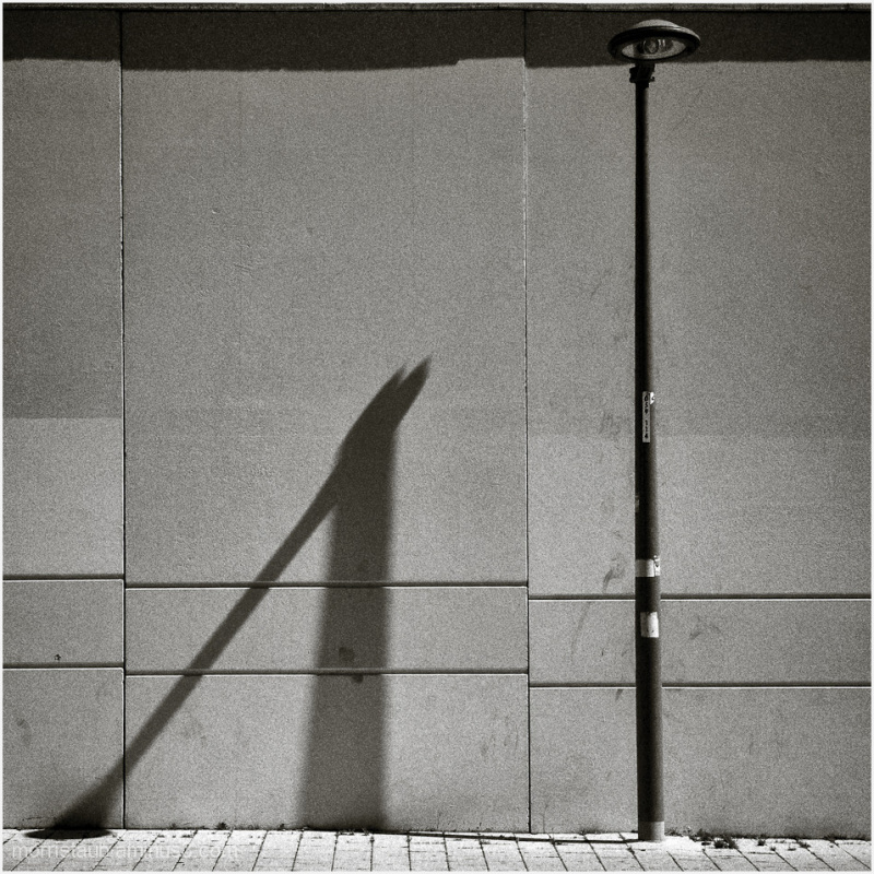 Street light and shadow on sunlit street.