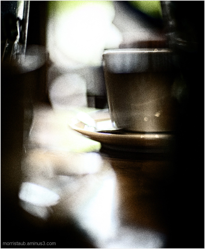 Cafe table with mug and glass blurred.