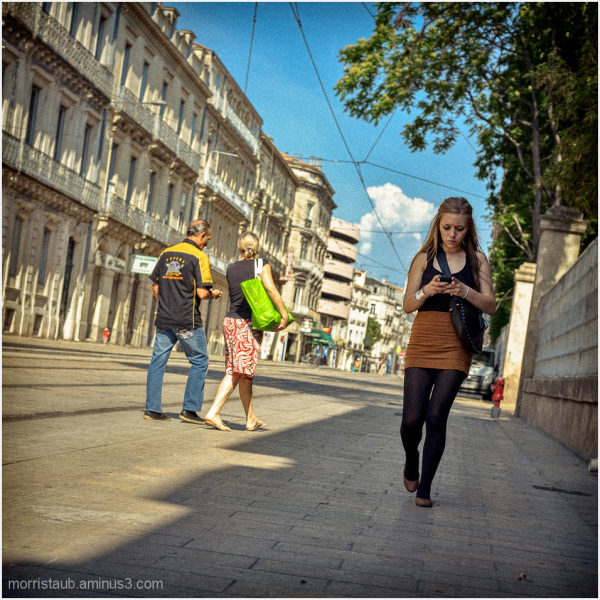 Young girl walking while checking her phone.
