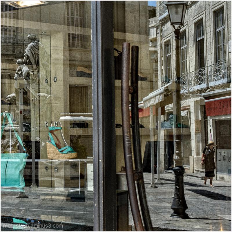 Old woman walking reflected in store window.