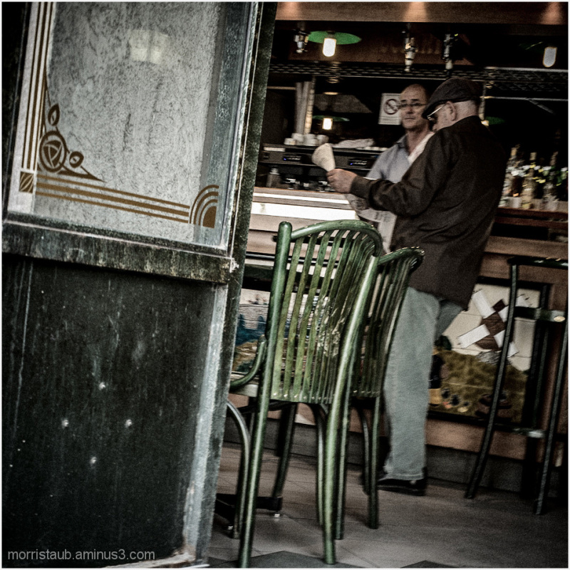 Old man reading a newspaper in an old cafe.