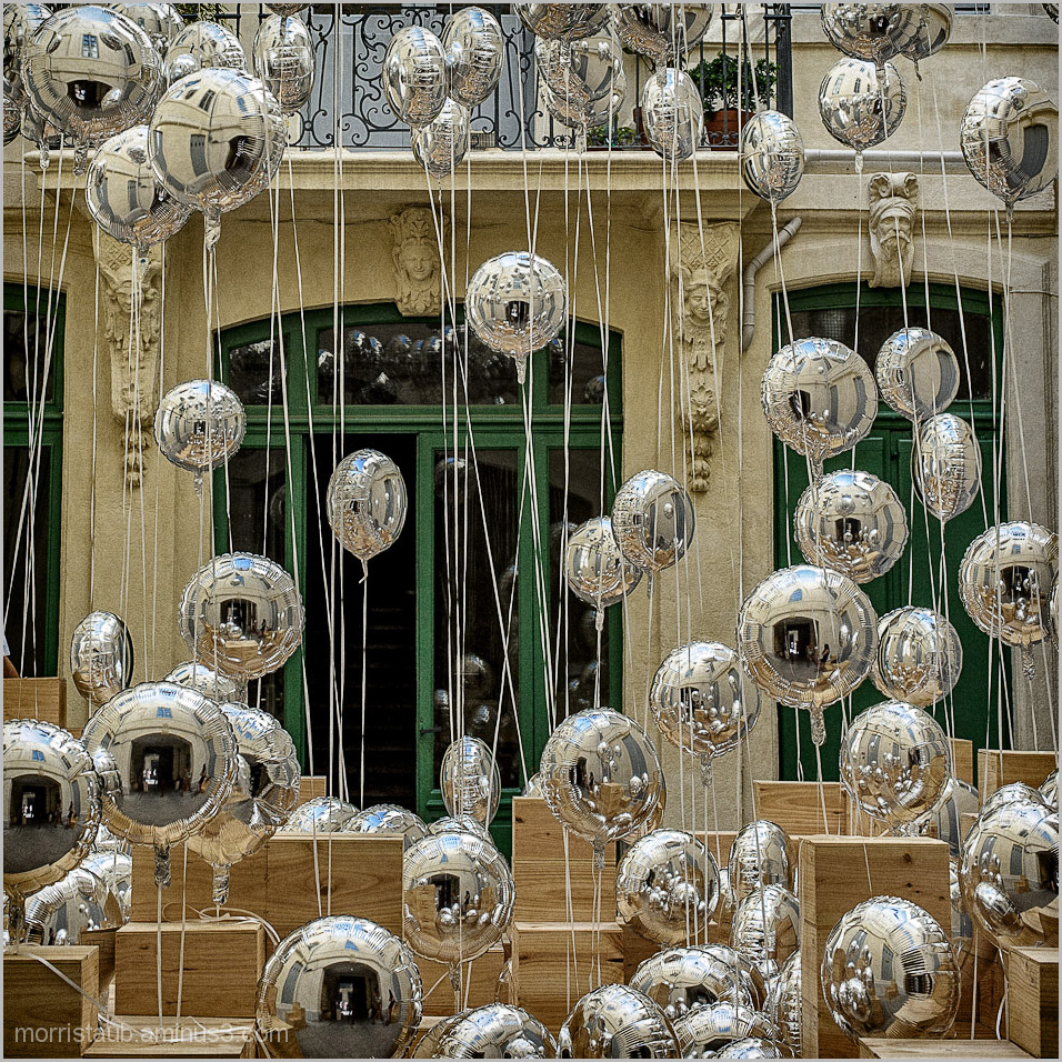 Silver balloon exhibit in courtyard.