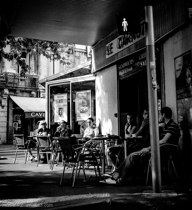 People having coffee outside a cafe.