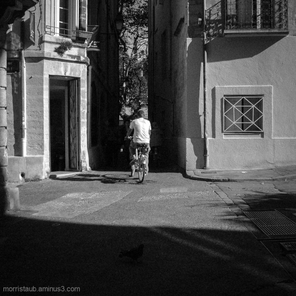 Cyclist heading down a shadowed street.