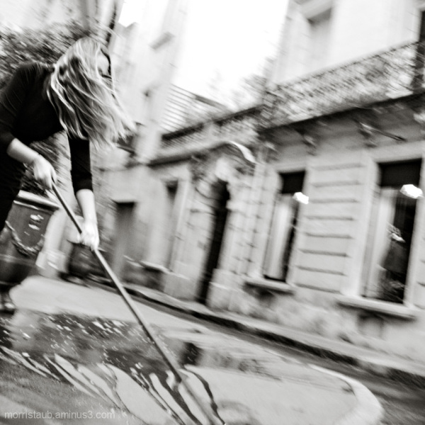 Woman sweeping the street hair blowing