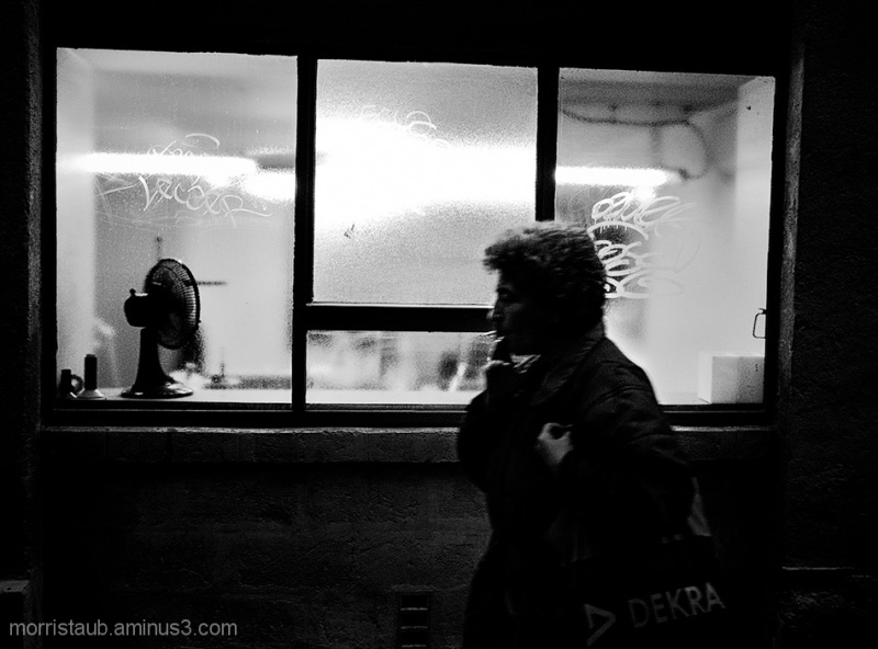 Woman walking by window smoking cigarette.