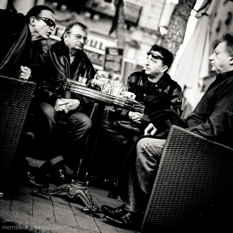 Four guys gathered for coffee.