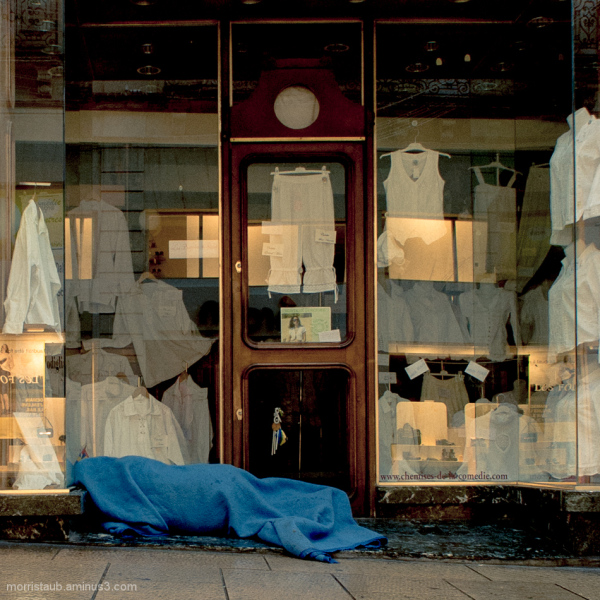 Homeless person wrapped in blue blanket.